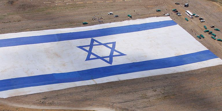 huge israeli flag lying on the ground viewed from the sky